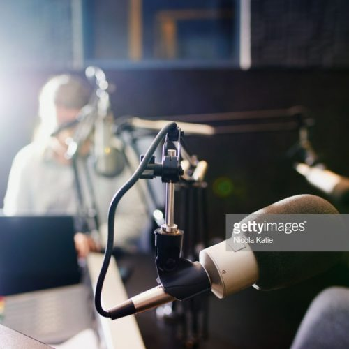 Shot of a microphone in a recording studio with the presenter blurred in the background